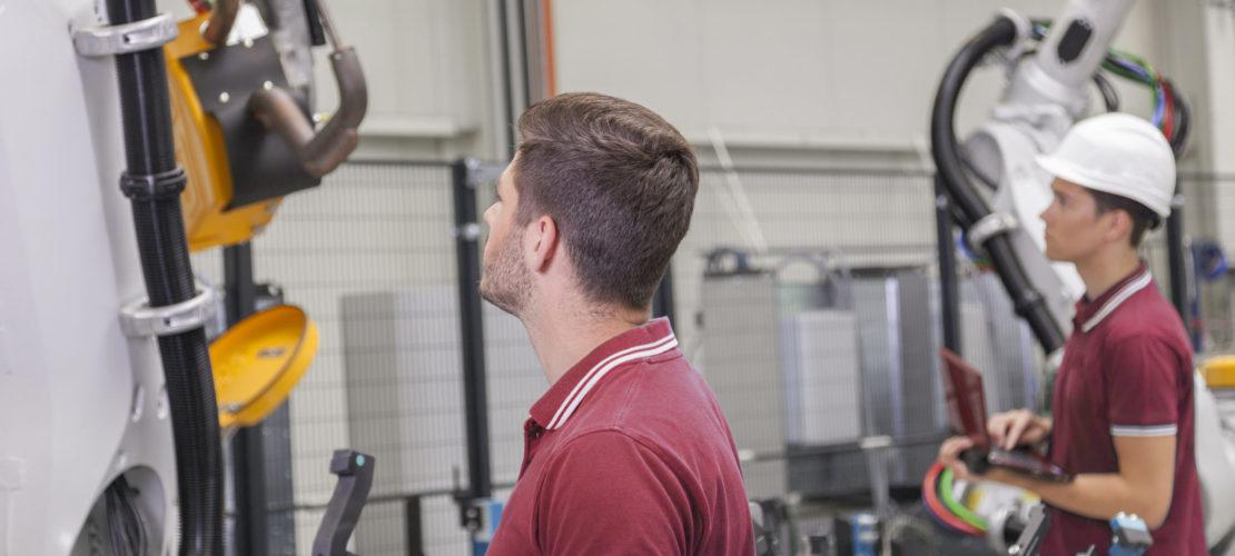 Maschinenbauingenieure prüfen einen Schweissroboter