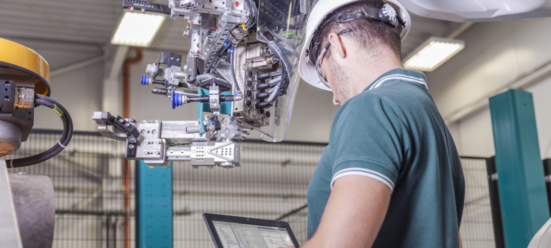 Maschinenbau Ingenieur mit Schutzhelm und Notebook bei der Inbetriebnahme eines Roboters
